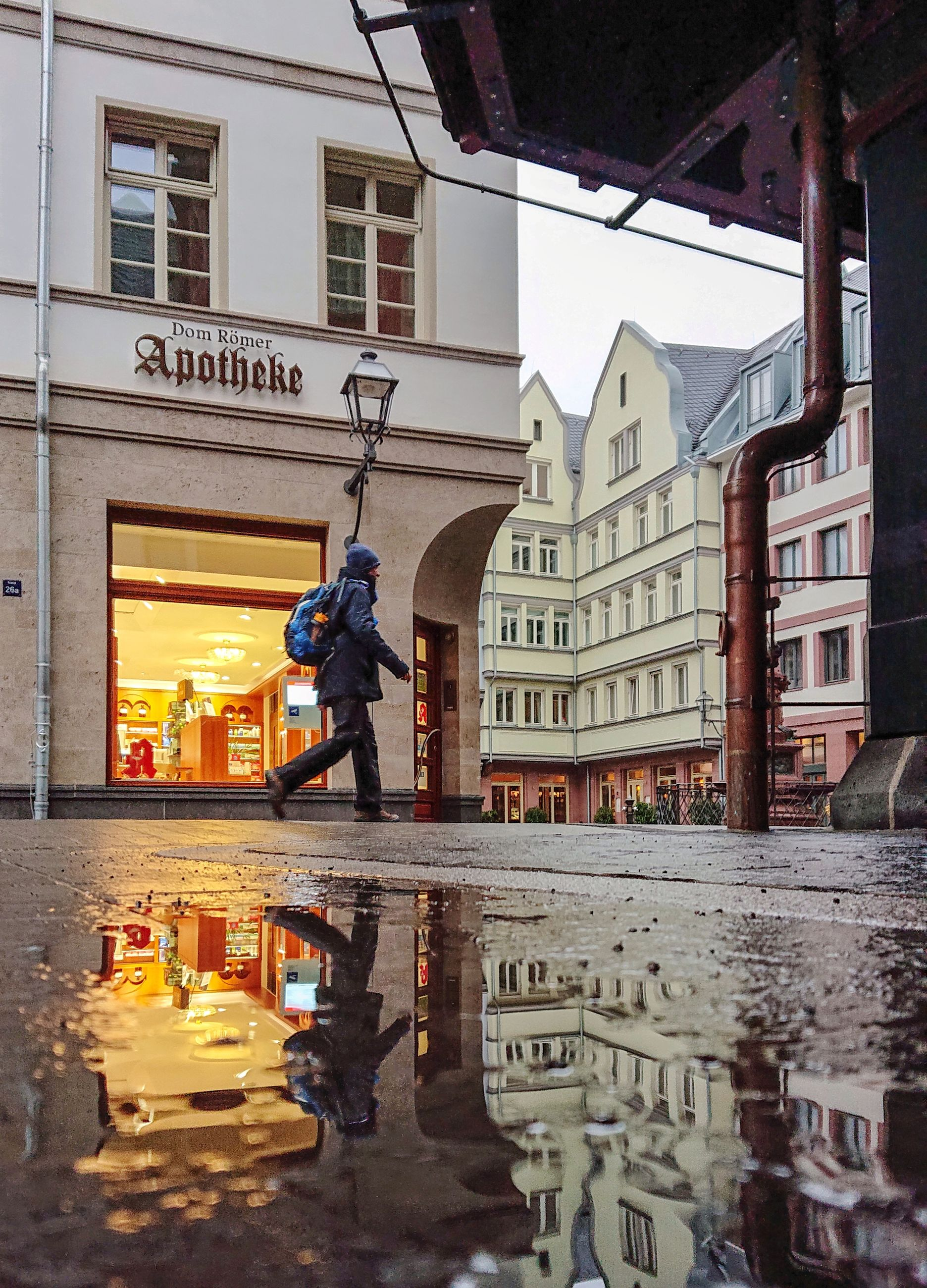 building exterior, architecture, built structure, city, one person, men, real people, full length, building, water, text, street, reflection, day, holding, standing, nature, incidental people, outdoors