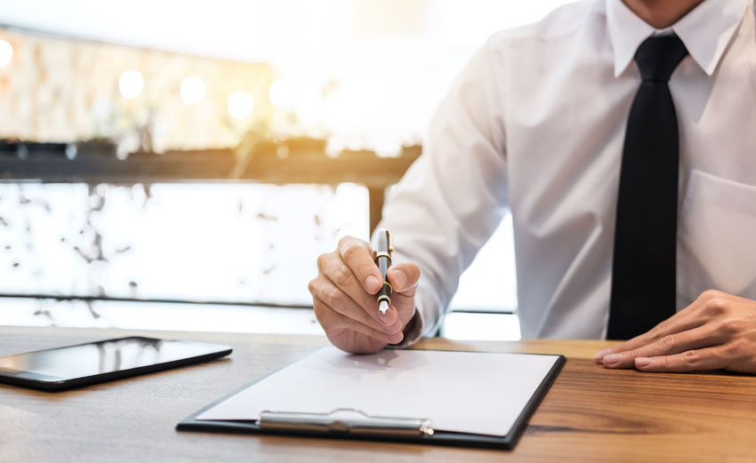 Midsection of businessman with pen and note pad working on desk