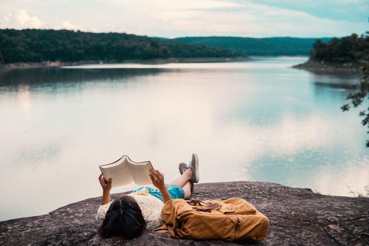 Woman sitting on rock by lake