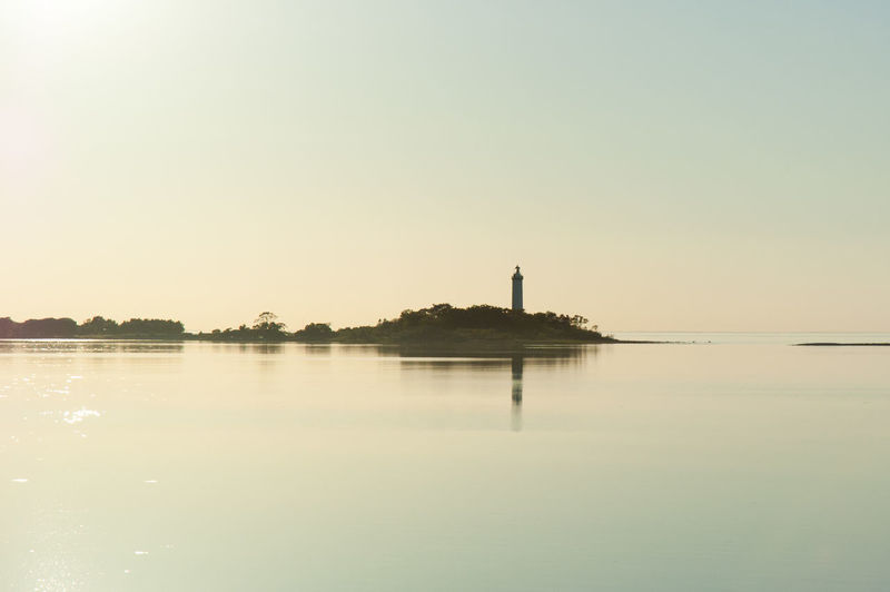 The silhouette of a lighthouse in the evening. Copy Space Water Sky Reflection Sunset Lighthouse Silhouette Evening Sea