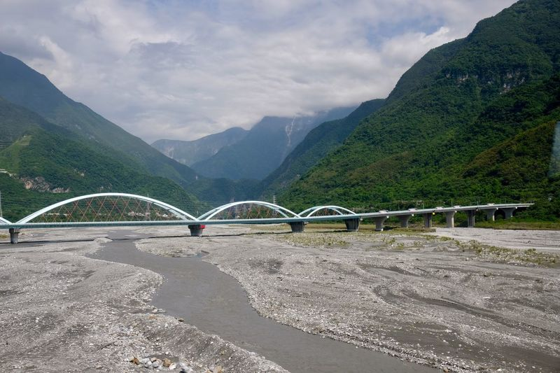 Scenic view of bridge over mountains against sky