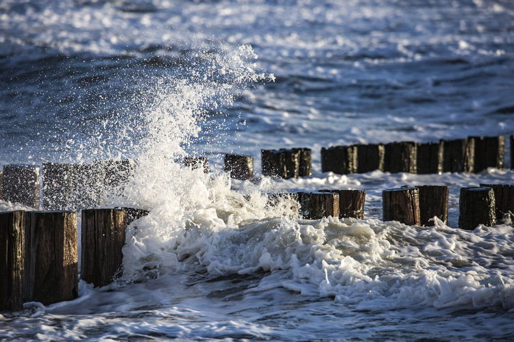 Close-up of water splashing on wooden post in sea
