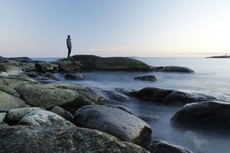 Side view of a man standing on rocks