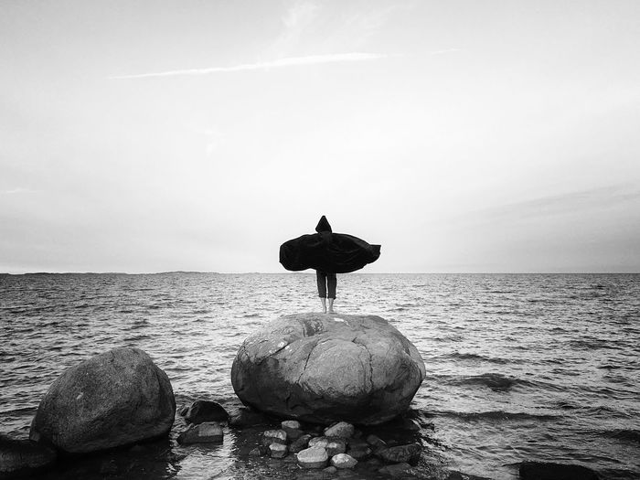 """""""learning to fly"""" Sea Horizon Over Water Water Tranquil Scene Escapism Rock - Object Getting Away From It All Carefree Cliff Ocean Standing Cape  Flutter Batman Escape Fly Away Blackandwhite Black And White Monochrome The Week Of Eyeem Found On The Roll Batmans Friends Watching The Ocean Standing On A Rock The Magic Mission"""