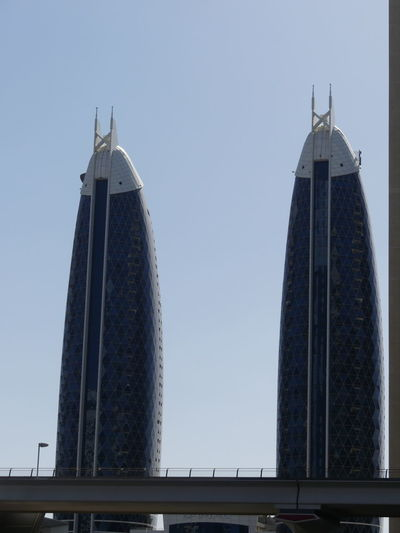 Two Buildings (based on the Gherkin in London structure?) on Sheik Zayed Road, Dubai, United Arab Emirates 2019 Dubai UAE 2019 Sheik Zayed Road Blue Sky Sunlight And Shade No People Low Angle View Two Towers Two Scyscraper Unusual Shape Modern Architecture Modern Design Architecture Metro Rail Building Facades Building Exteriors Silos Tall - High Composition Outdoor Photography City Towers Skyscrapers Tourist Destination