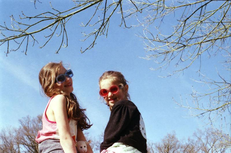 Portrait Of Happy Siblings Wearing Sunglasses Against Blue Sky