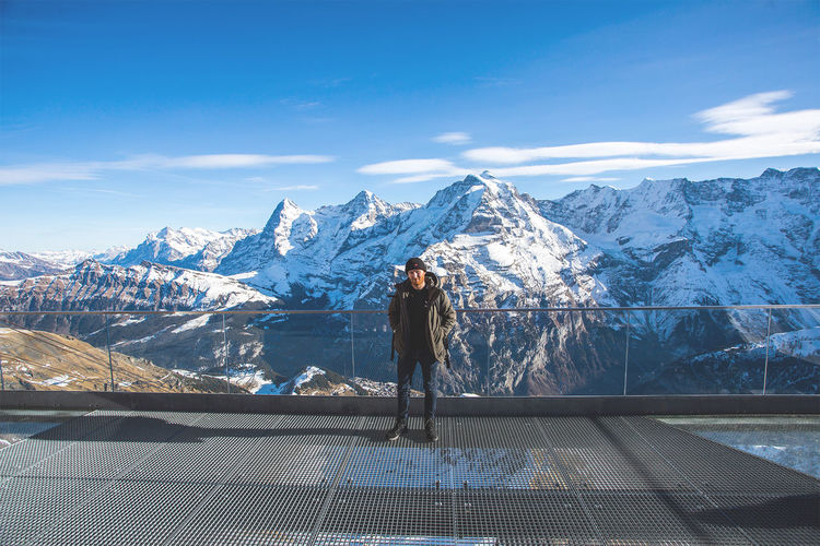 Hiker Standing On Observation Point Against Snowcapped Mountains