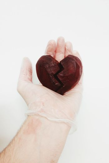 Hand holding beet in broken heart shape against white background