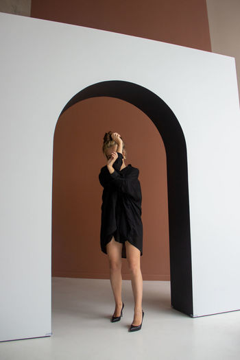 Full length rear view of woman standing against wall