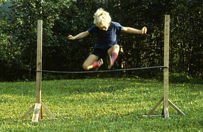 A Boy High Jumping Always Higher! Arms Outstretched Blond Hair Day Grass I Made It! Jou Of Life Jumping Motion Outdoors Summer Track And Field Vitality