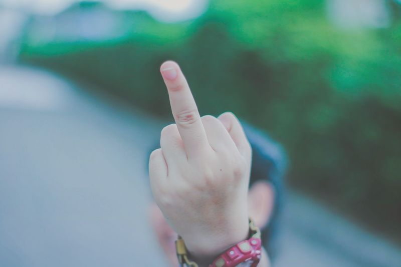 Close-up of person showing middle finger