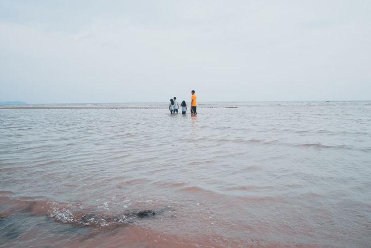 Men standing on beach against sky