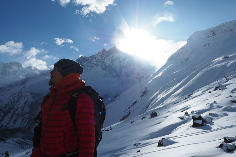 Backpacker Standing Against Snowcapped Mountains