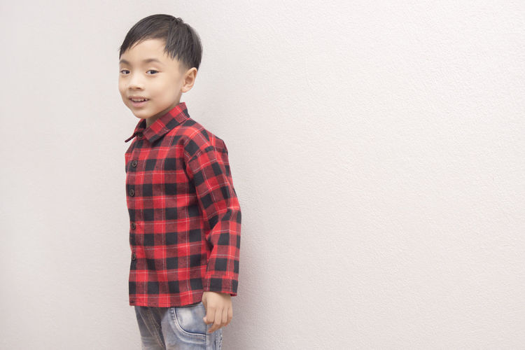 Portrait Of Smiling Boy Standing Against White Wall