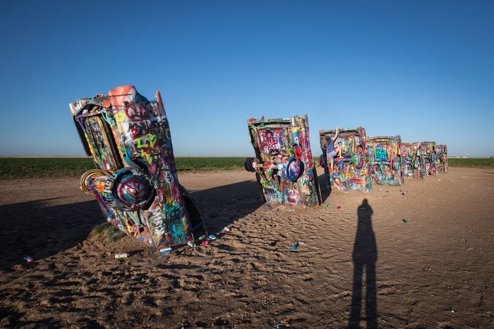 Viewing Cadillac Ranch in early morning light Cadillac Ranch Amarillo Texas Shadow Graffiti Cadillac Graffiti Art Light And Shadow Single Person Colorful Cars In The Ground Route 66 Roadside Attractions Roadtrip Original Experiences
