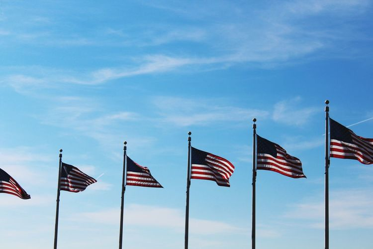 American flags waving against blue sky