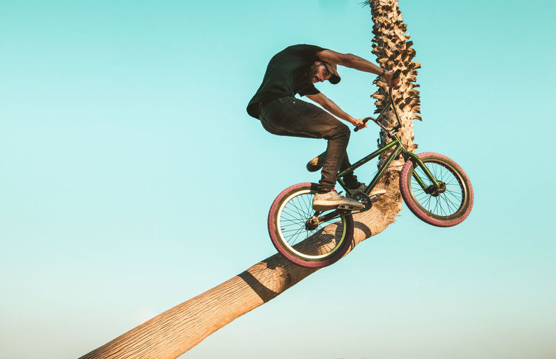 Low angle view of man jumping bicycle against clear sky