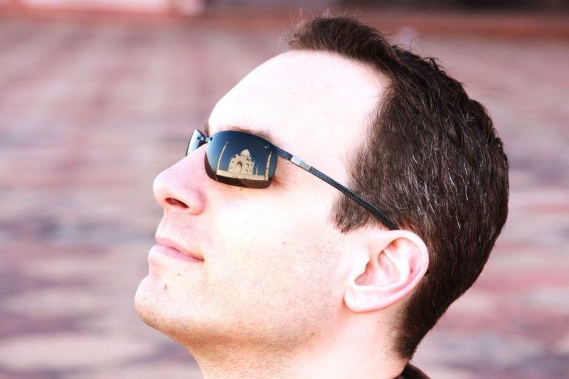 Man with reflection of taj mahal on sunglasses