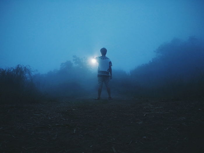 Rear view of man with illuminated light standing on land against sky at night