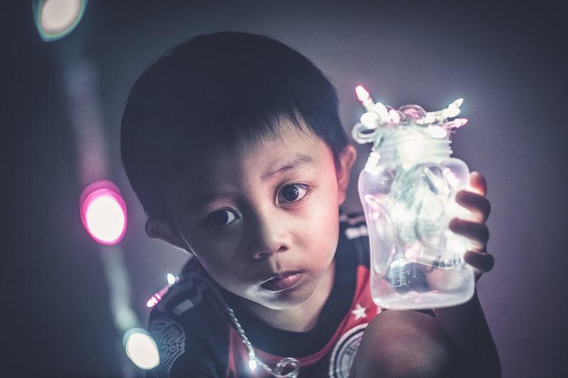 Close-up of boy holding jar of fairy lights