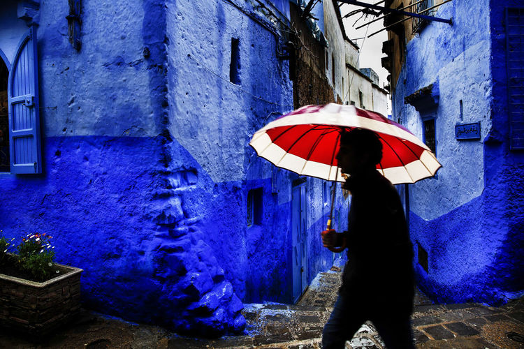 Red umbrella Blue Umbrella One Person Architecture Day Wet Outdoors Rain Rainy Day Blue City Chefchaouen Red Umbrella The Art Of Street Photography