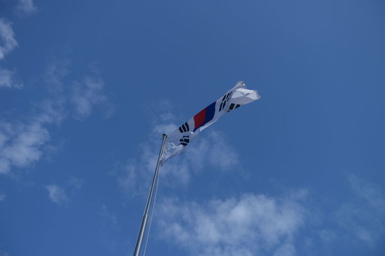 Sky Low Angle View Cloud - Sky Patriotism Nature Flag Blue Day No People Environment Flying White Color Wind Outdoors Waving Pole Tranquility Transportation Motion National Icon Independence Plane Korean Flag