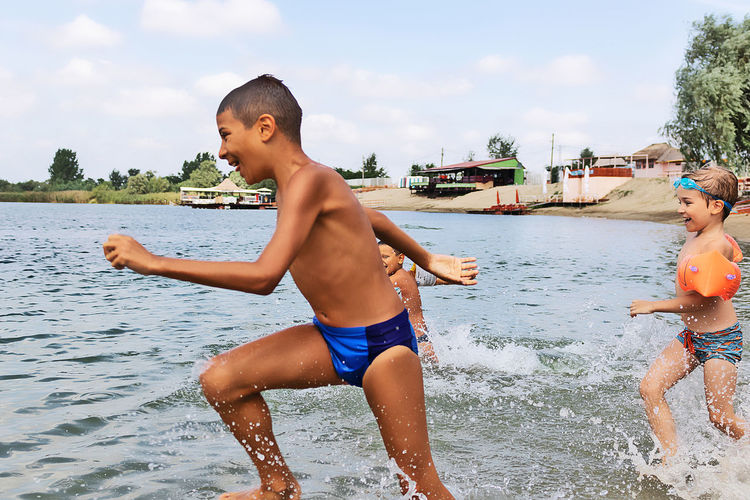 Full length of shirtless boy in water against sky