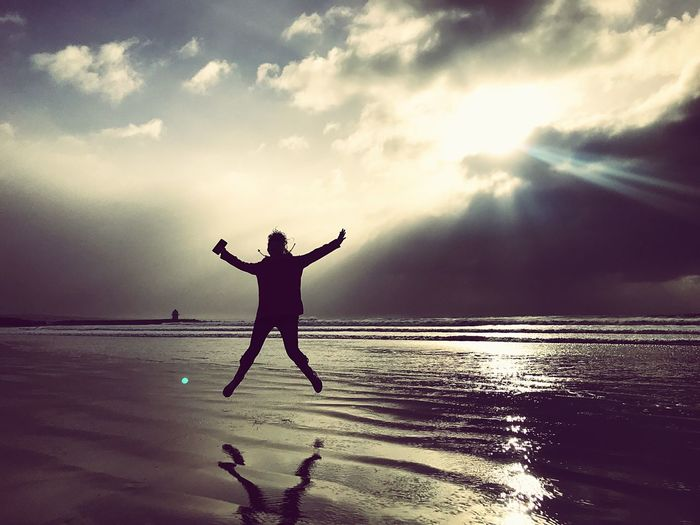 Jump Stormy Skies Sky Water Cloud - Sky Sea Human Arm Land Beauty In Nature Real People Silhouette One Person Beach Lifestyles Arms Raised Horizon Over Water Holiday