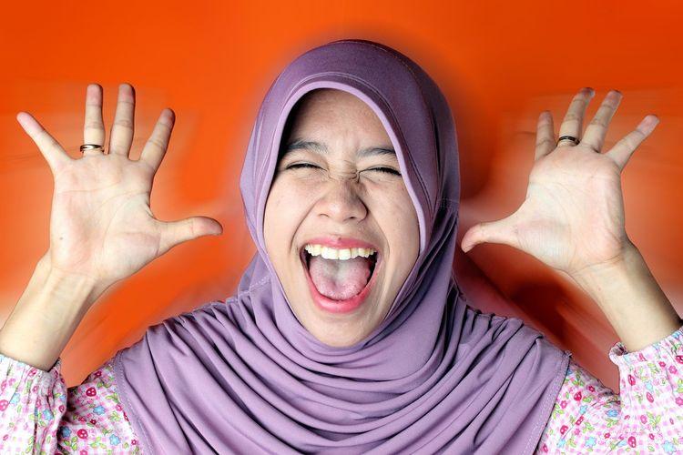 Studio shot of girl in hijab screaming against orange background