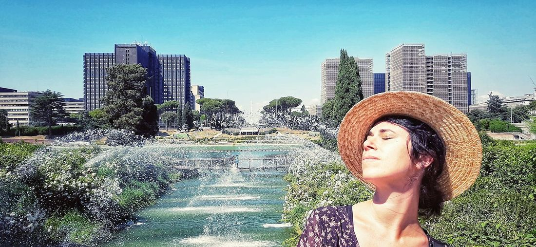 Portrait of beautiful woman in city against sky