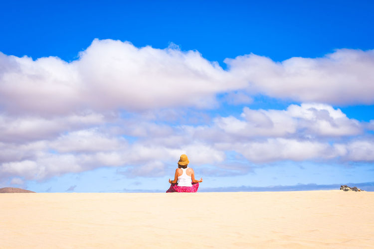 Beautiful young girl sitting alone on the white sand of a tropical beach in Fuerteventura. Colorful exotic vacation postcard. Blue sky and clouds in backgruond. Youth lifestyle freedom travel concept Adult Back Beach Beauty Calm Canary Caucasian Clouds Coralejo Cute Dunes Exercise Female Health Healthy Holiday Island Isolation Leisure Life Lifestyle Meditation Mind  Morning Natural Nature Ocean One Outdoor Outdoors Peace People person Portrait Pose Relax Relaxation Sea Sky SPAIN Spirit Spirituality Summer Sun Training Tranquility White Woman Yoga
