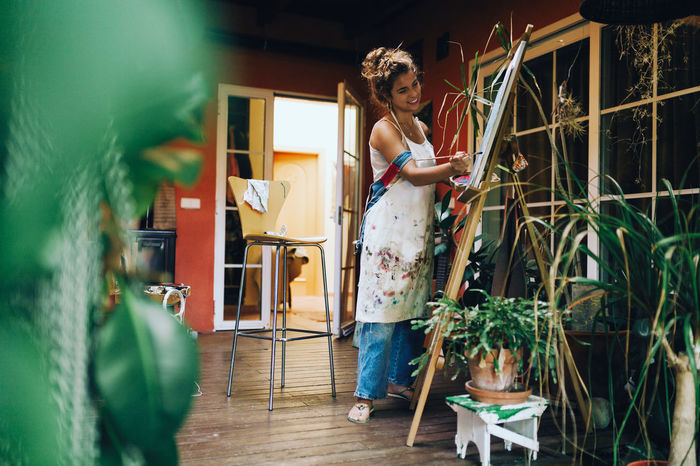 WOMAN STANDING BY POTTED PLANTS AT HOME
