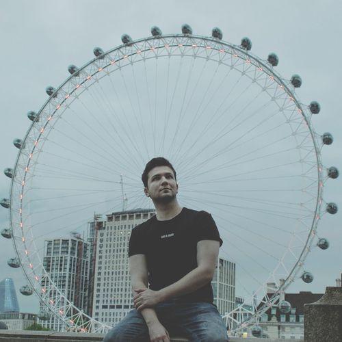 Portrait of man with ferris wheel against sky