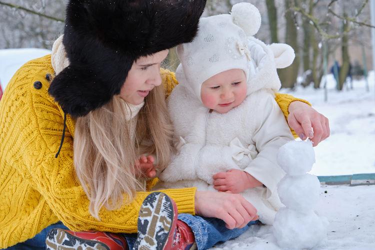 Full length of cute girl sitting in snow