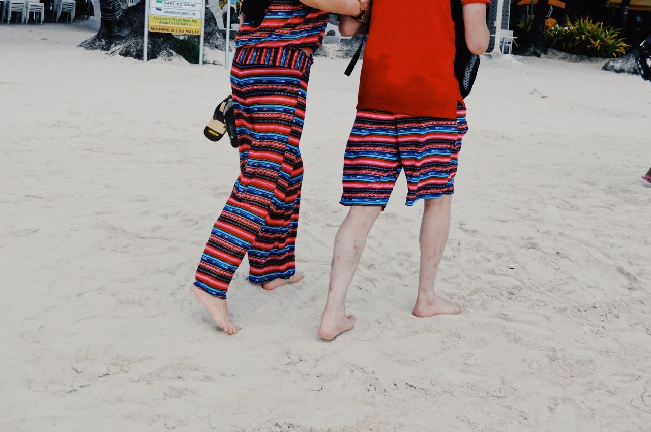 Low section of couple walking on sandy beach
