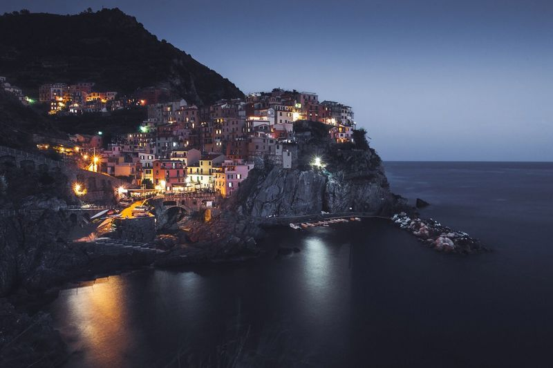 Buildings by sea in vernazza at night