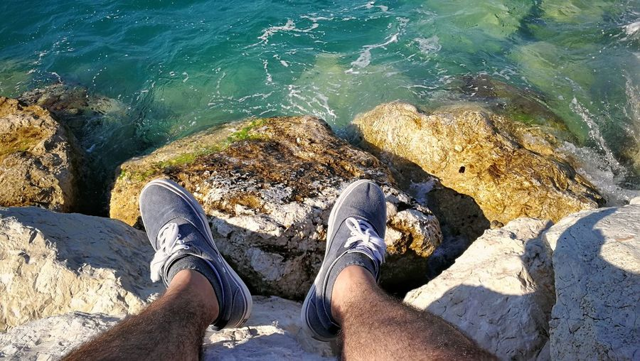 Low section of man sitting on rock at sea