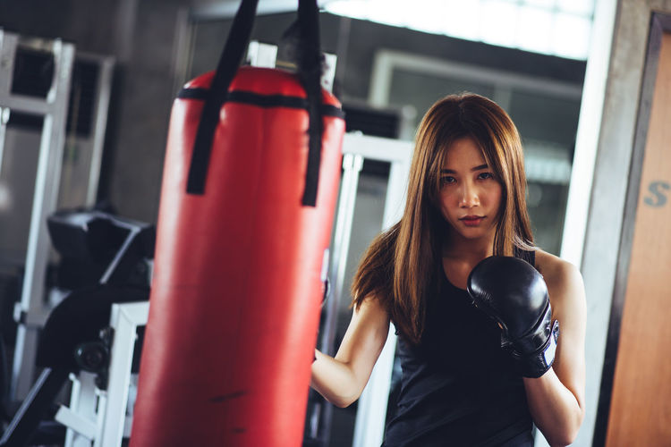 Portrait Of Young Woman Practicing Boxing With Punching Bag In Gym