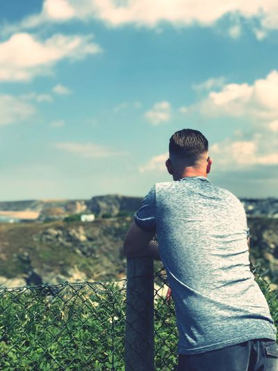 Rear View One Person Real People Lifestyles Leisure Activity Day Nature Sky Men Casual Clothing Water Cloud - Sky Land Three Quarter Length Sunlight Outdoors Focus On Foreground Beauty In Nature Sitting Looking At View
