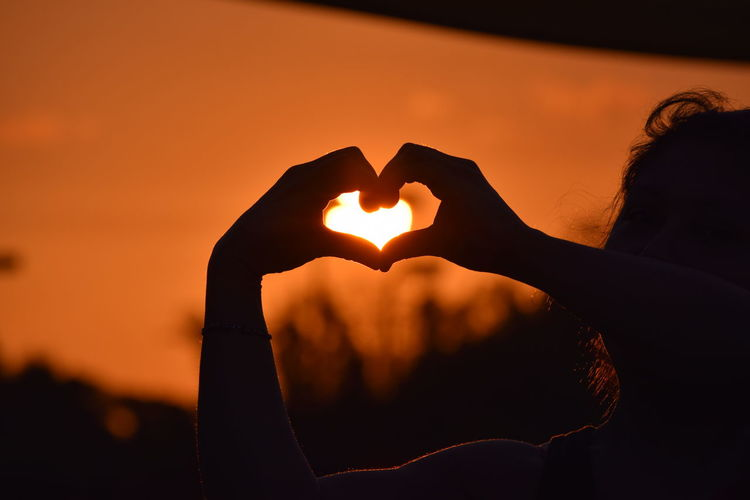Woman making heart shape against sky during sunset