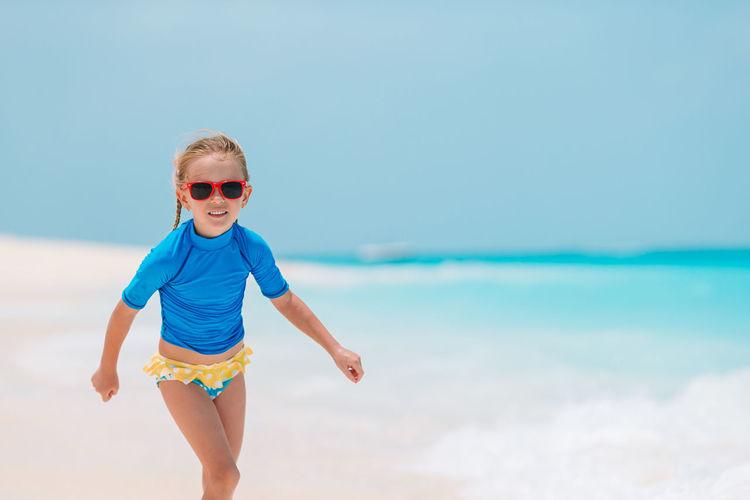 Boy wearing sunglasses on beach against sky