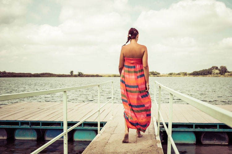Back view of woman in sun dress walking on a pier at the beach. copy space.