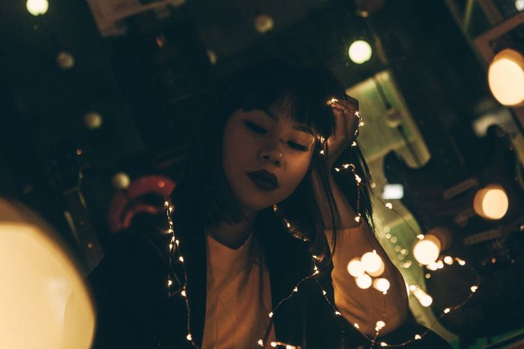 Young Woman With Illuminated String Lights Sitting In Room