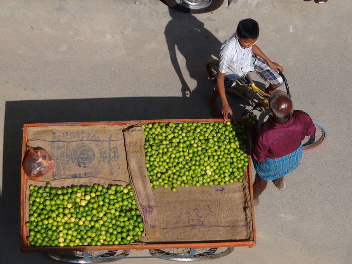 High angle view of boy buying lemons from market vendor on street in city during sunny day