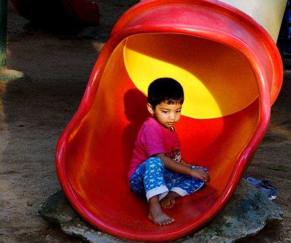 Cute Boy Sitting On Tunnel Slide