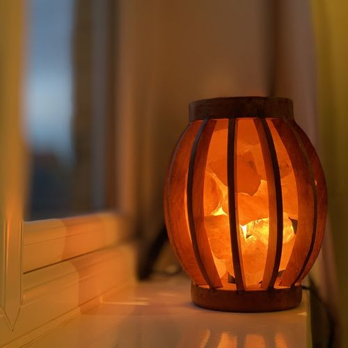Close-up of illuminated lamp on window sill at home