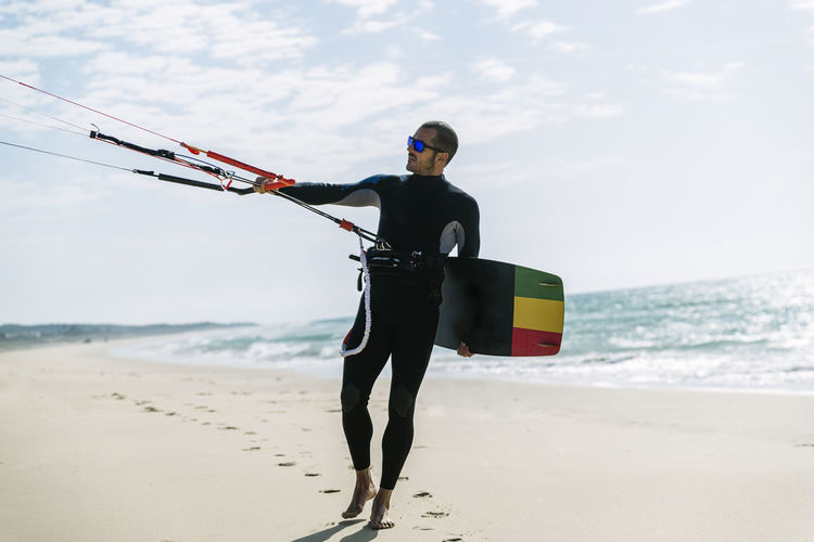 Man with kiteboard standing at beach