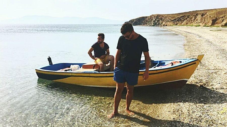 Men in boat on beach against sky