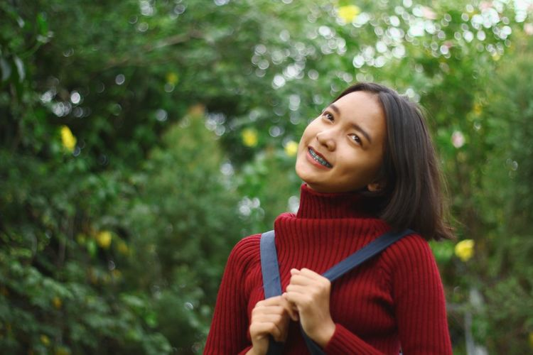 Smiling teenage girl against trees in forest