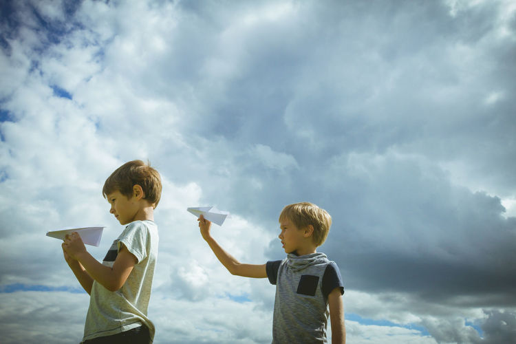 Siblings playing with paper airplanes against cloudy sky